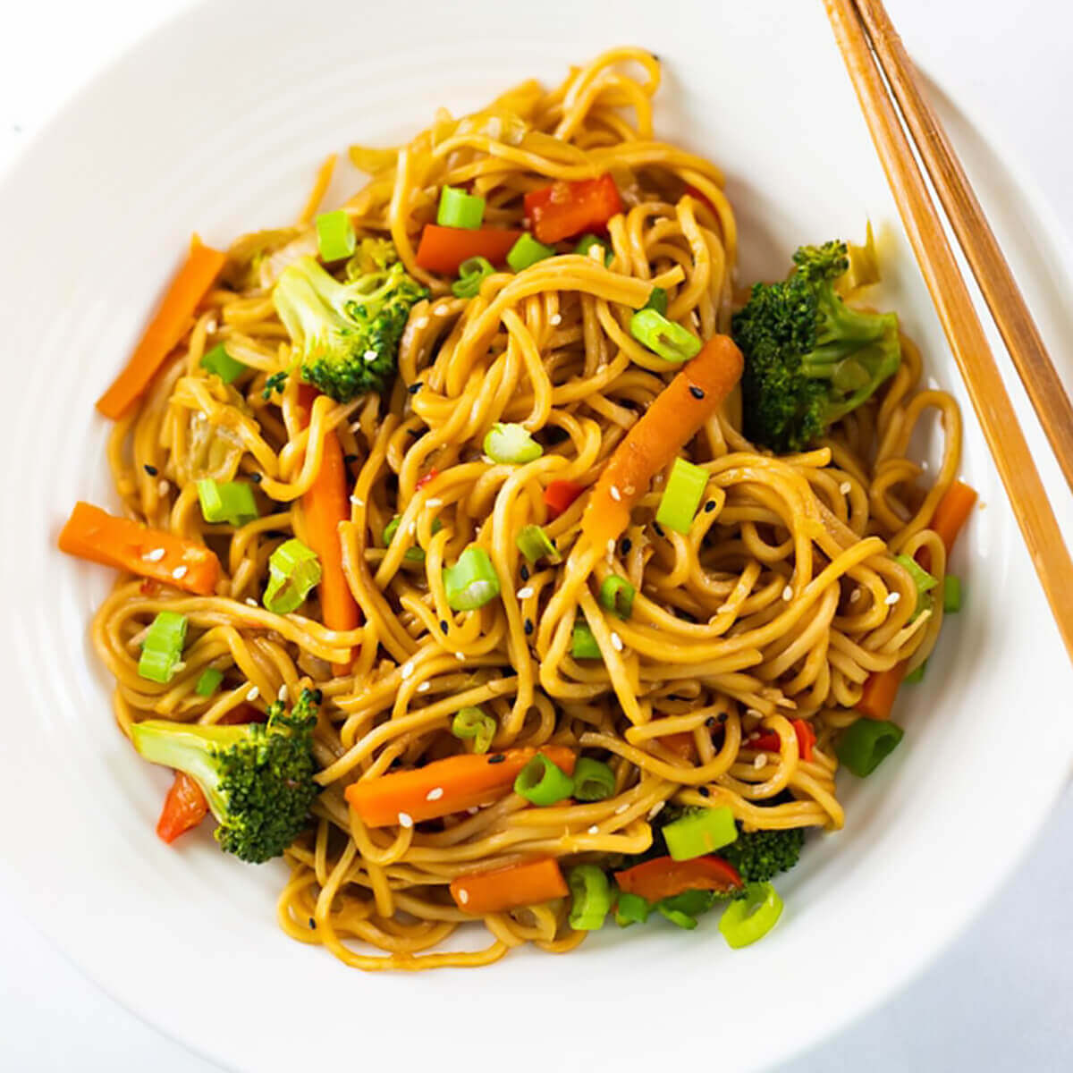 Vegetable lo mein served with chopsticks.