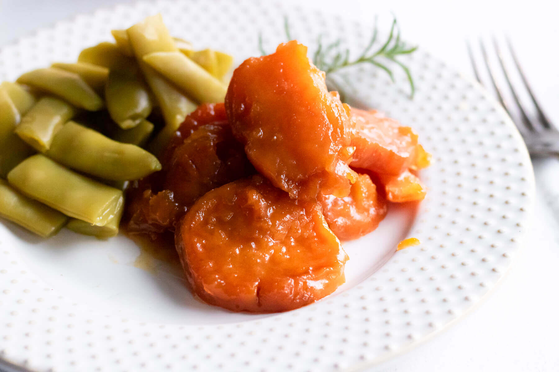 Candied Sweet Potatoes on white plate served with a side of green beans.