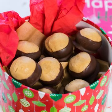 Homemade Buckeye Candy in pretty red container for gifting.