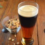 Black and Tan cocktail in a pilsner glass served with peanuts.