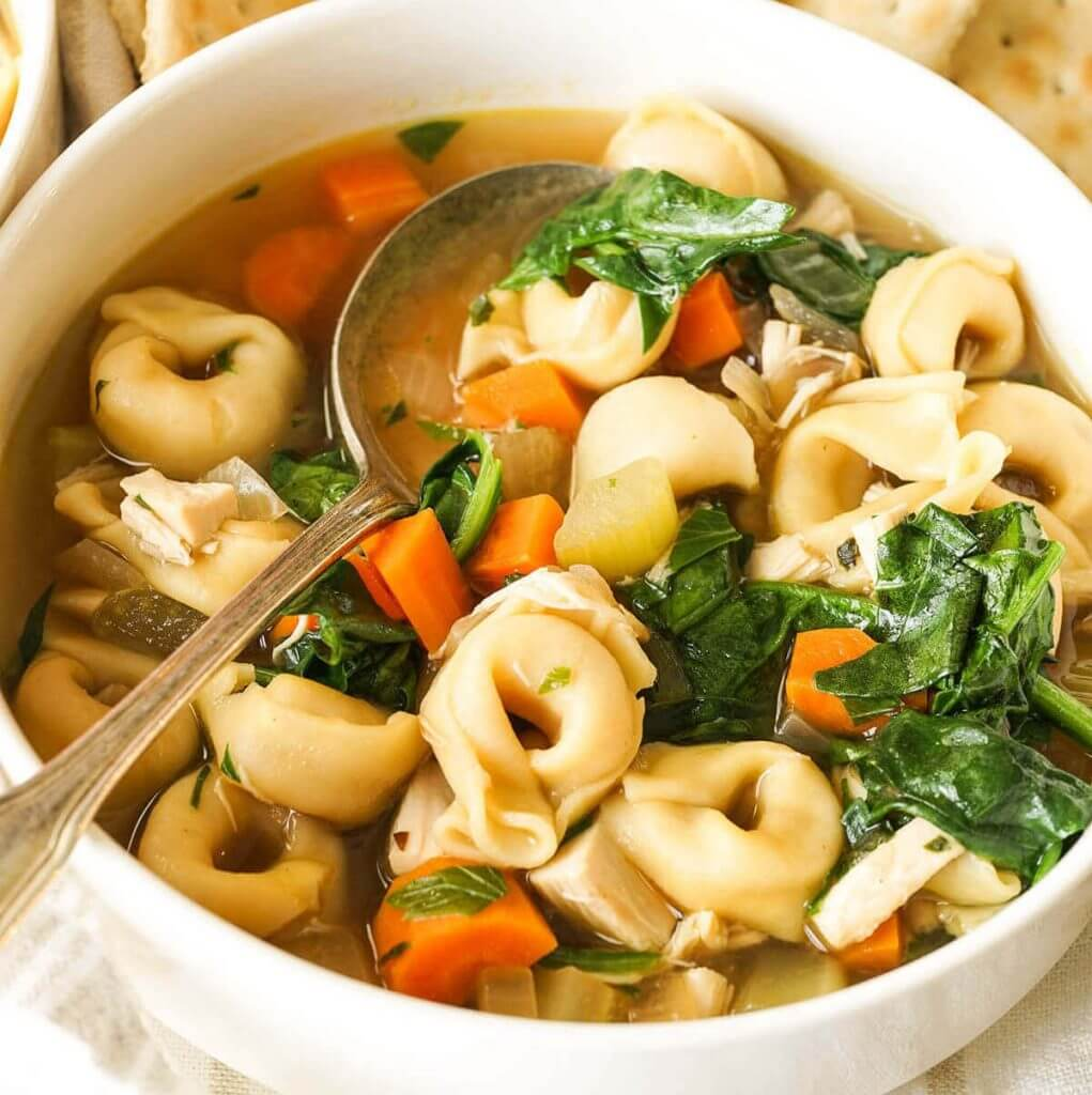 A white bowl filled with chicken tortellini soup with spoon.