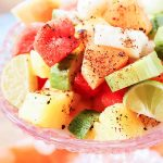 Mexican Fruit Salad topped with Tajin in pink bowl.
