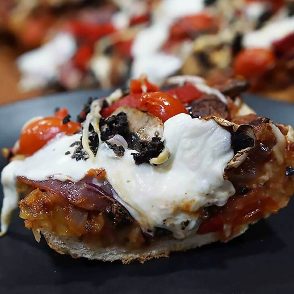 A slice of pizza bread with olives and tomatoes and topped with melted mozzarella cheese.