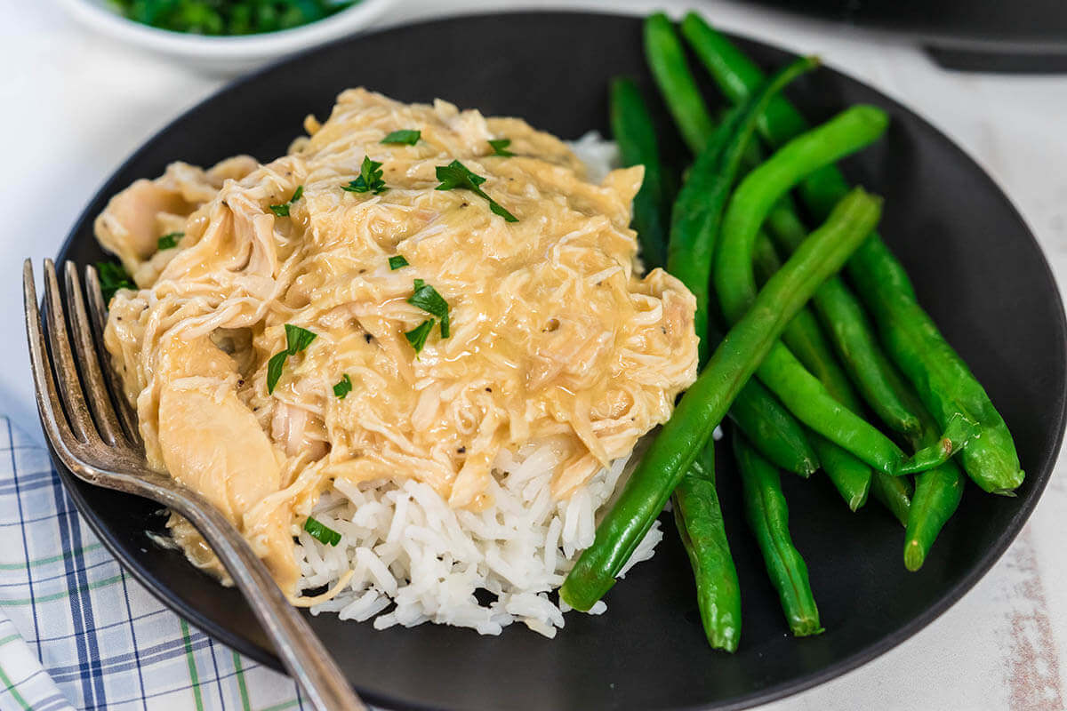 Chicken and Gravy over rice with green beans on black plate.