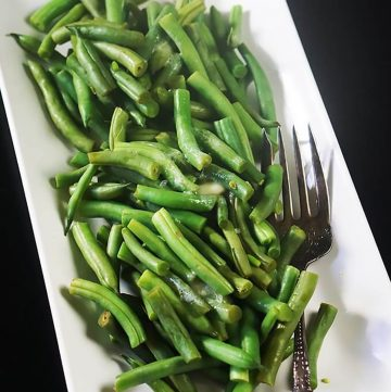 Microwave steamed green beans on white platter with serving fork.