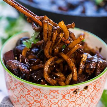 jajangmyeon noodles in a bowl being served with chopsticks.