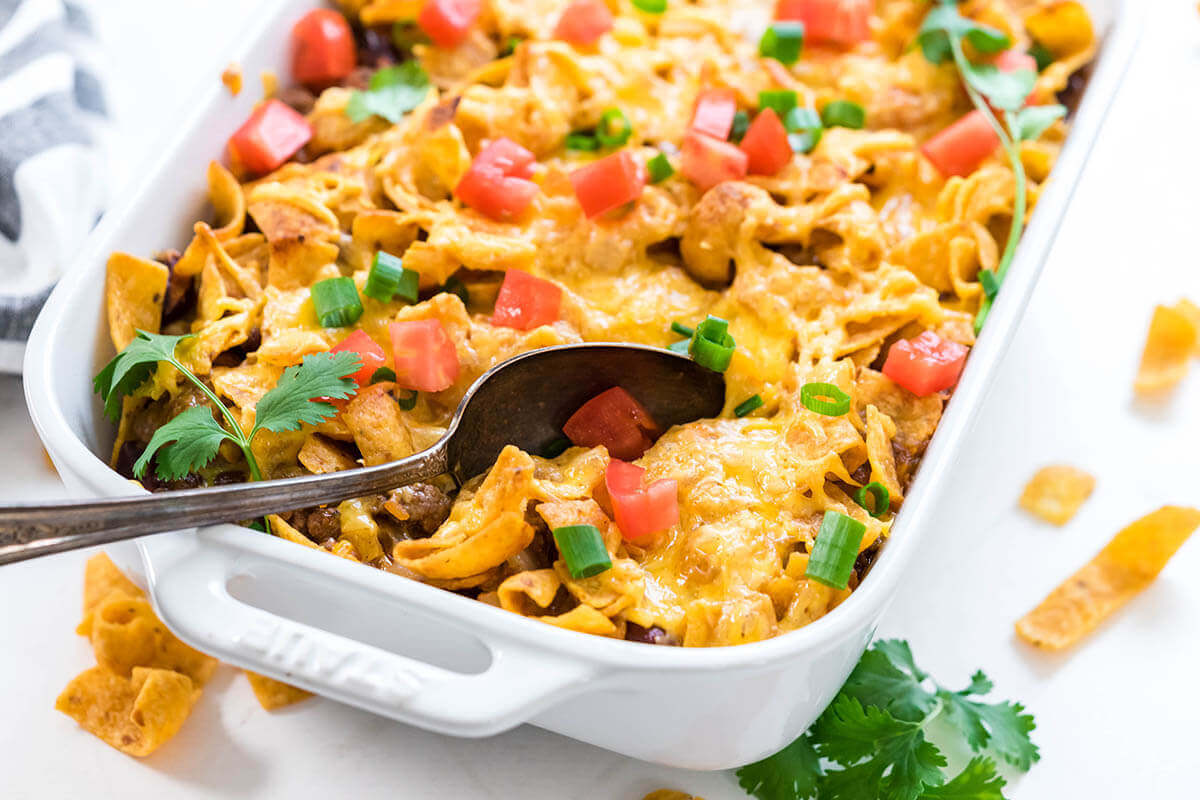 Frito Taco Pie in white casserole dish topping with melted cheese with serving spoon.