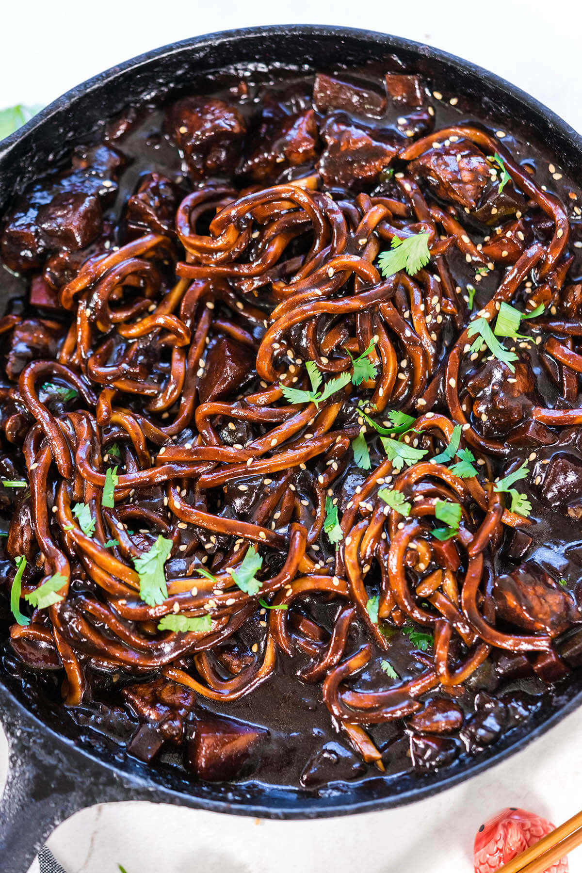 Korean Black Bean Noodles in a skillet topped with cilantro and sesame seeds.