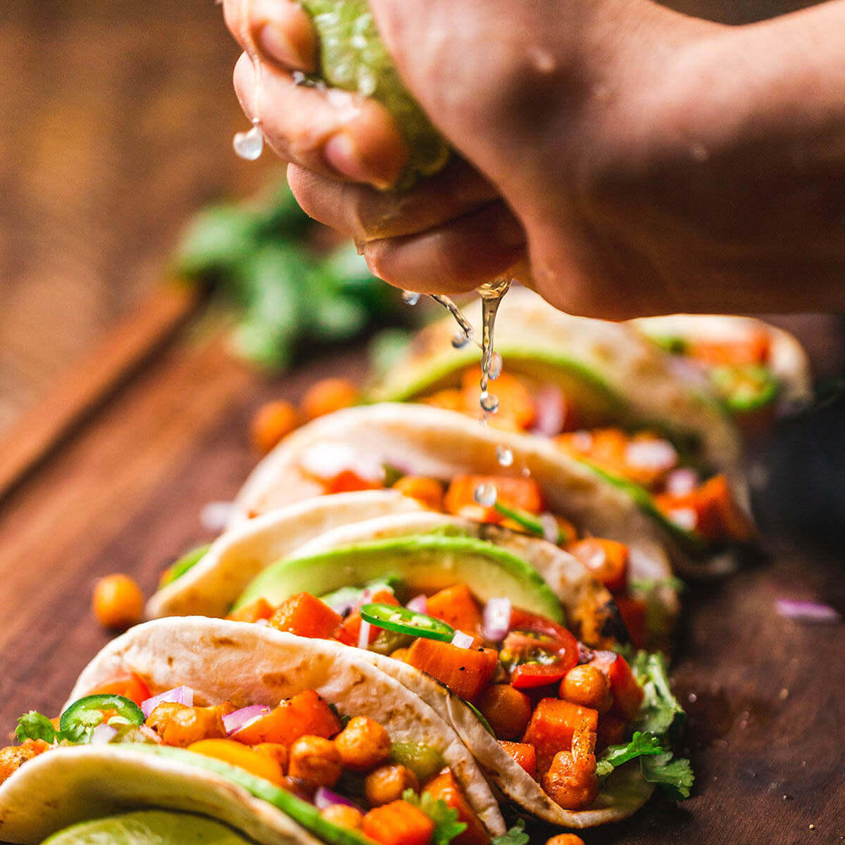 Tacos lined up and topping with all the fixings, there's a hand squeezing fresh lime over all the tacos.