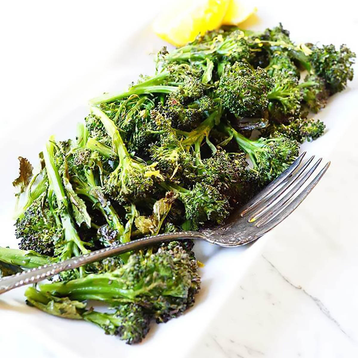Roasted broccoli on white plater with lemon.