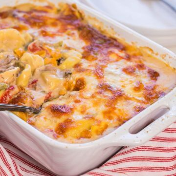 Baked Tortellini in white casserole dish with spoon.