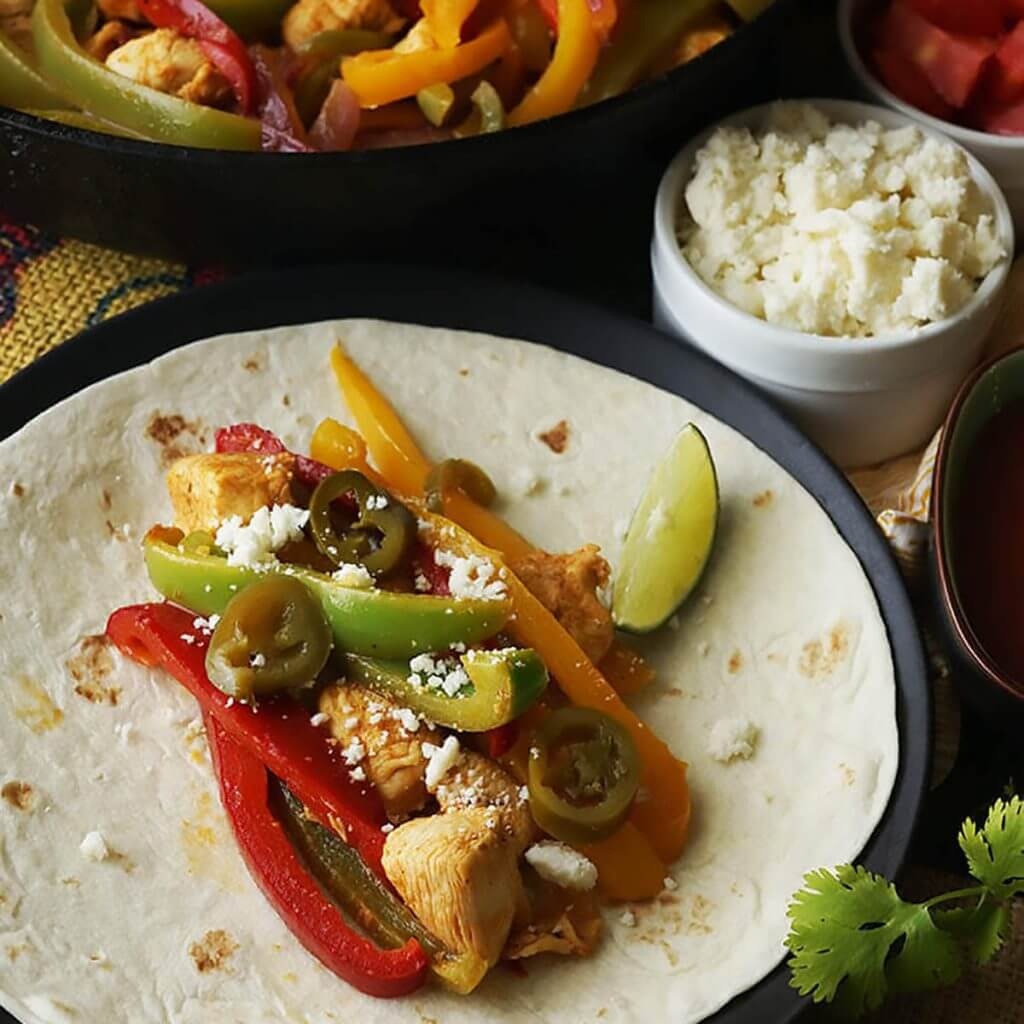 Chicken Fajitas on flour tortilla topped with cheese and lime.