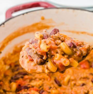 Chili Mac n Cheese in Dutch oven with a scoop on a wooden spoon.