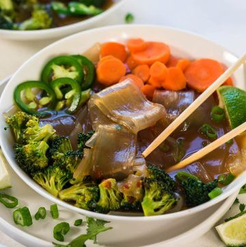 Vegetable soup in white bowl served with chopsticks and garnished with sliced green olives.