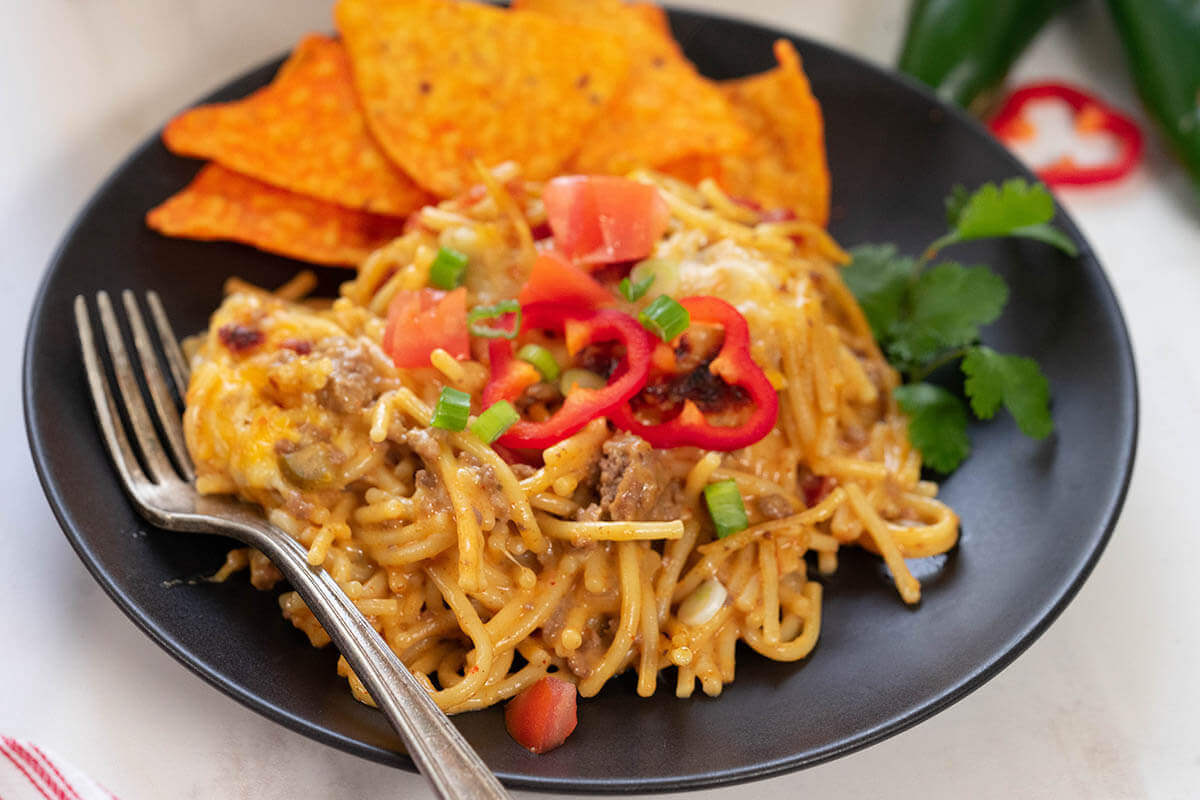 Taco spaghetti served with Doritos chips on black plate with fork.