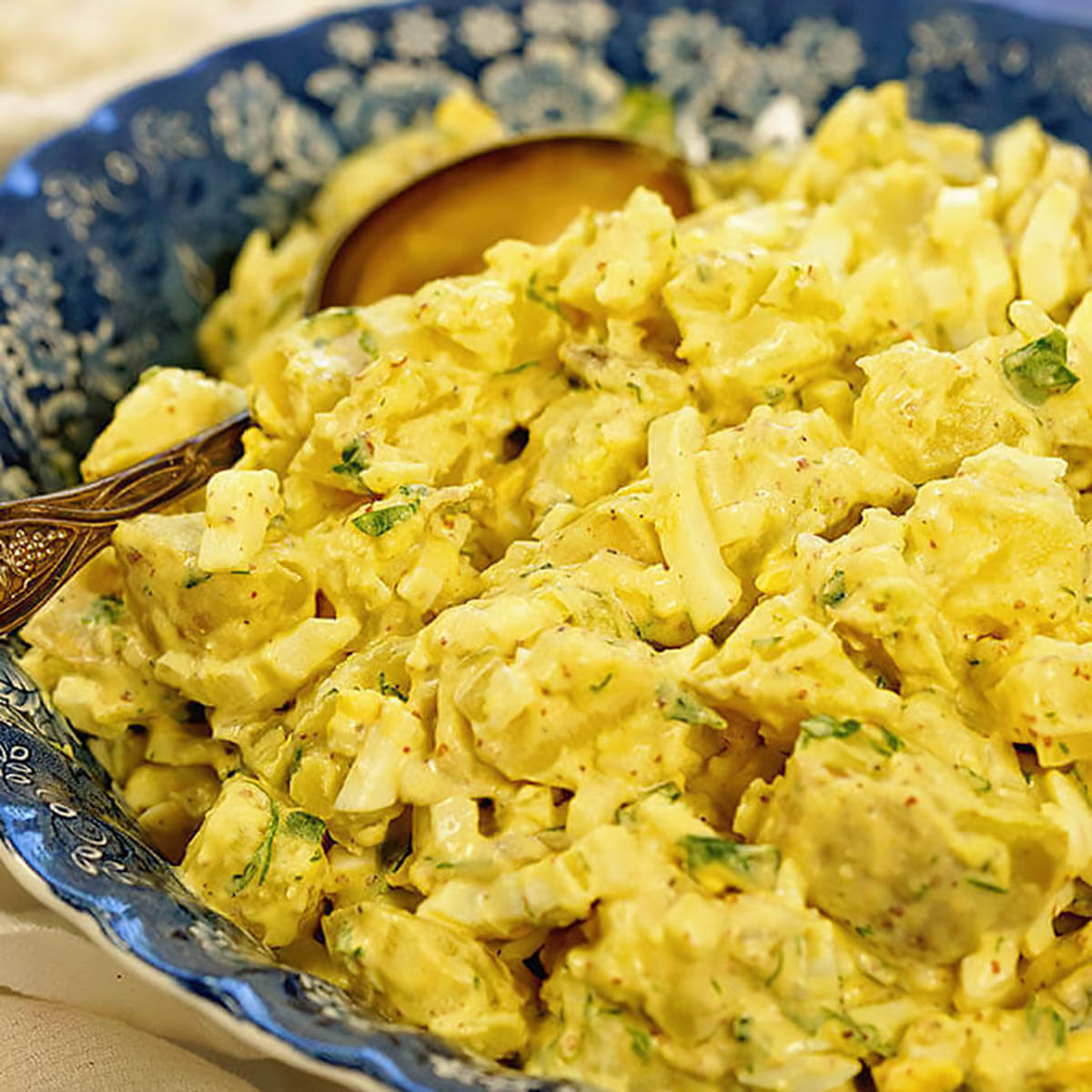 Deviled Egg Potato Salad in blue bowl with serving spoon.