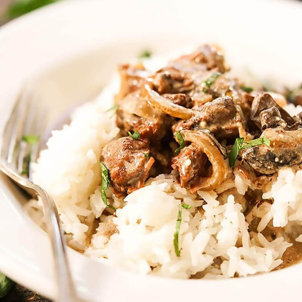 Beef Stroganoff in a white bowl over rice.