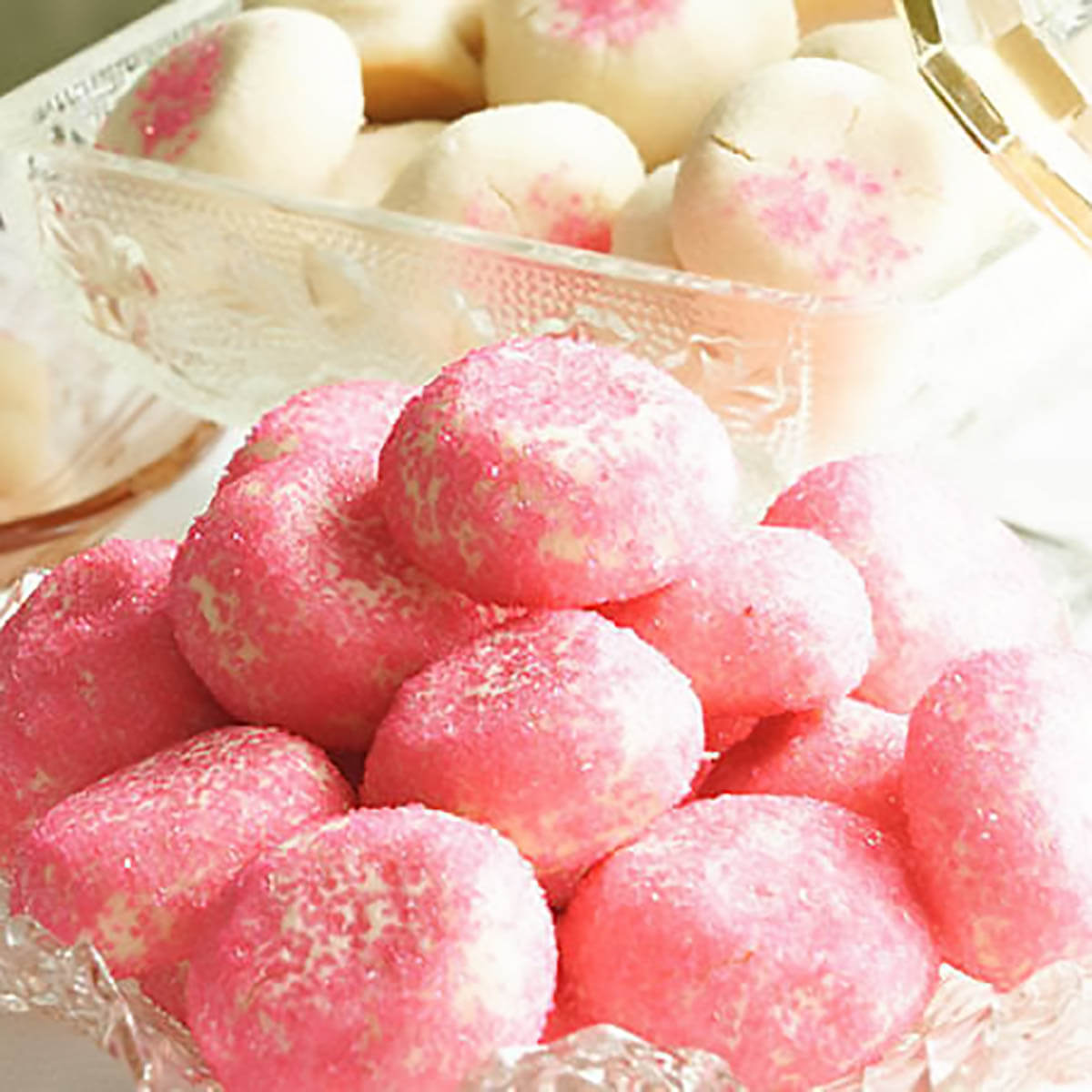 Butter cookies with pink sprinkles in glass bowl.