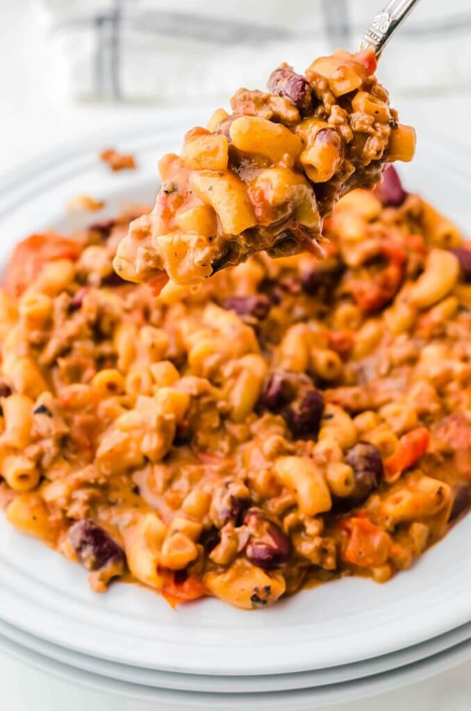 A heaping bowl of cheesy chili Mac n Cheese with a spoon taking a big scoop.