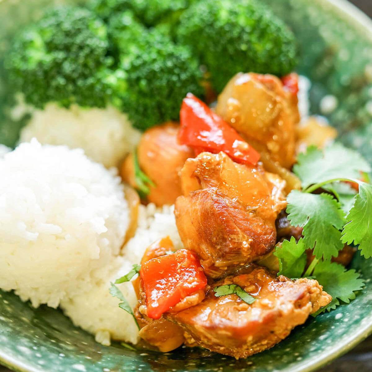 Honey sriracha chicken served with rice and broccoli in bowl.
