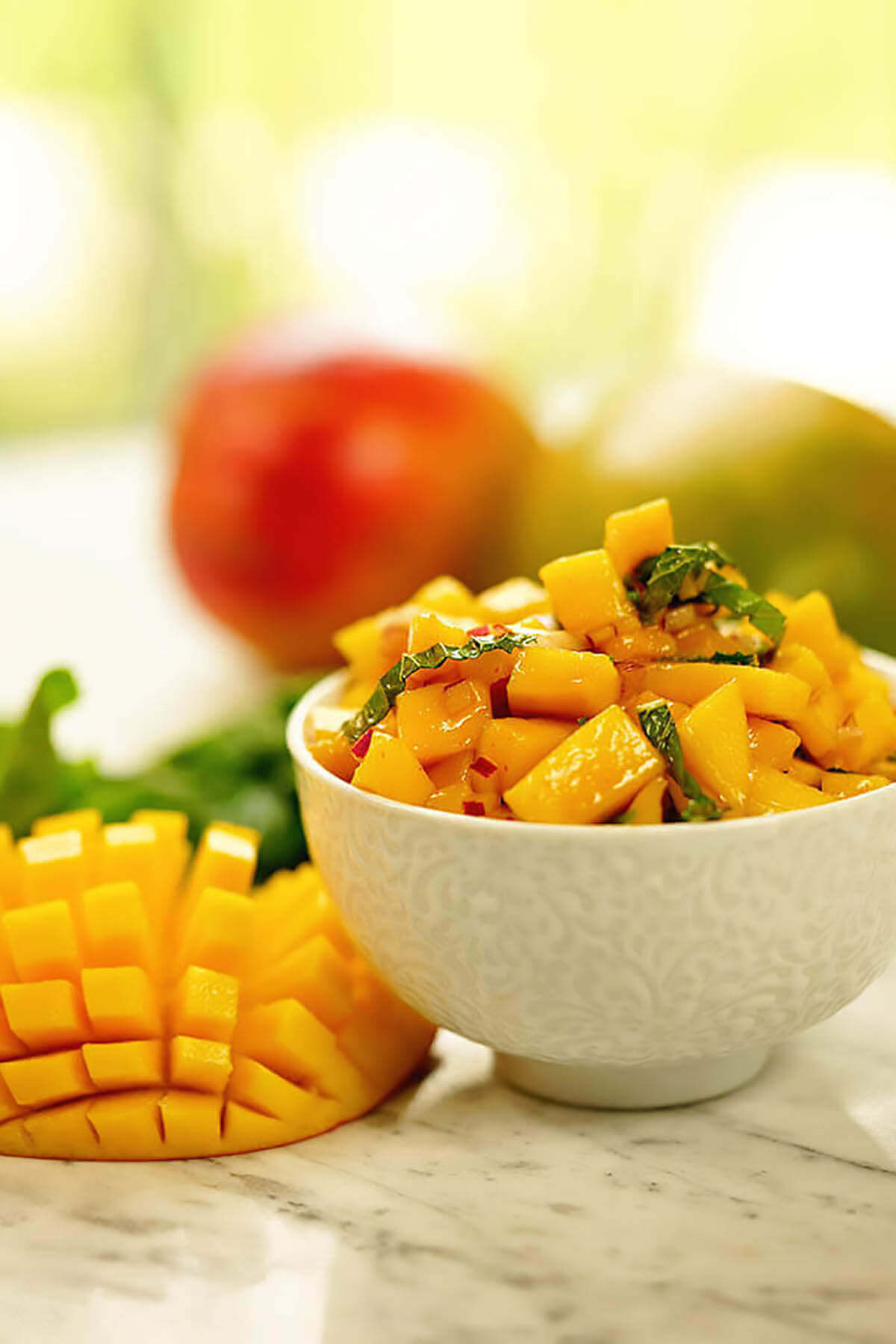 Spicy mango salsa in bowl with more diced mango alongside.