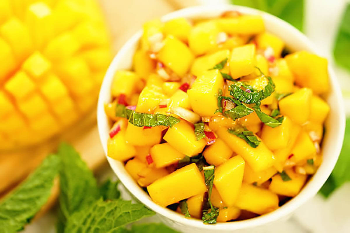 Mango Salsa in white bowl topped with mint. More diced salsa is laying on the side.