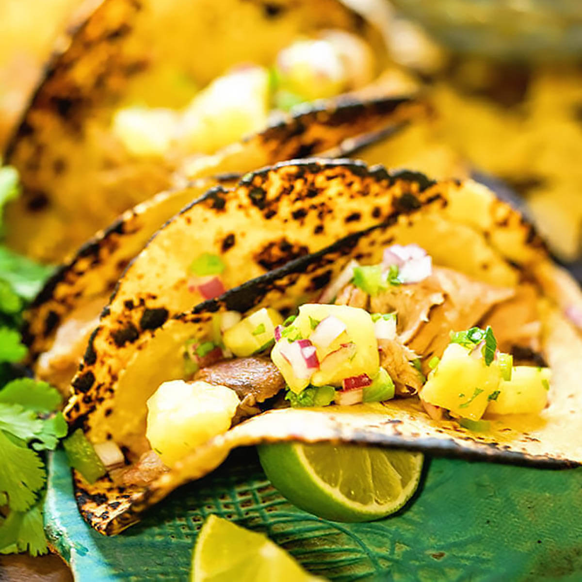 Pork tacos topped with pineapple salsa.