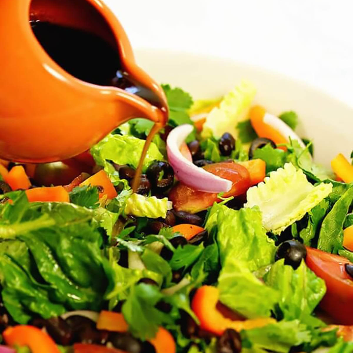 Salad dressing being poured over a green salad.
