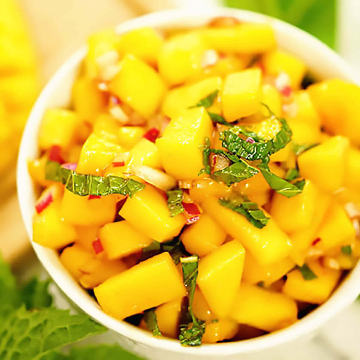 Spicy Mango Salsa in white bowl topped with mint.