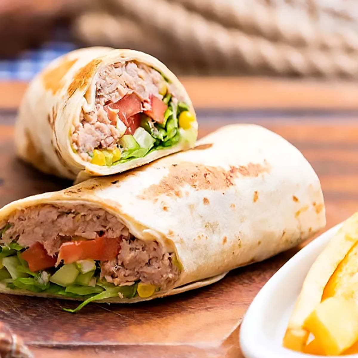 Tuna Sandwich wrap on plate served with fries.