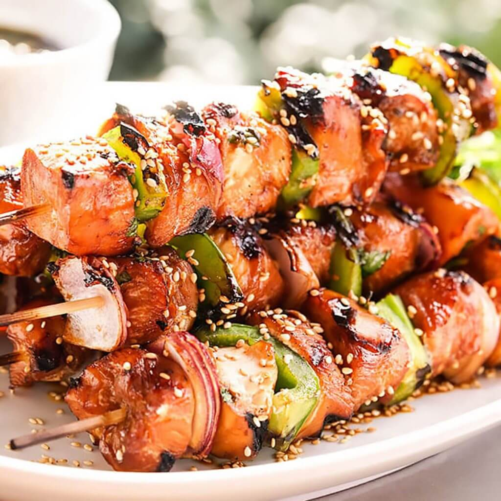 A stack of grilled teriyaki chicken kabobs on platter.