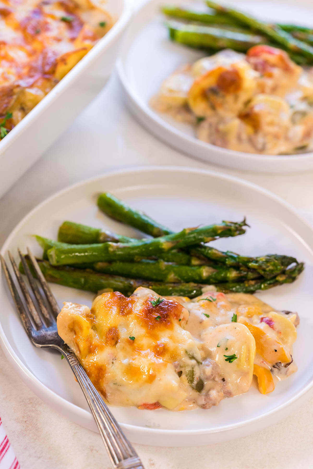 Baked Cheese Pasta with asparagus on white plate with fork.