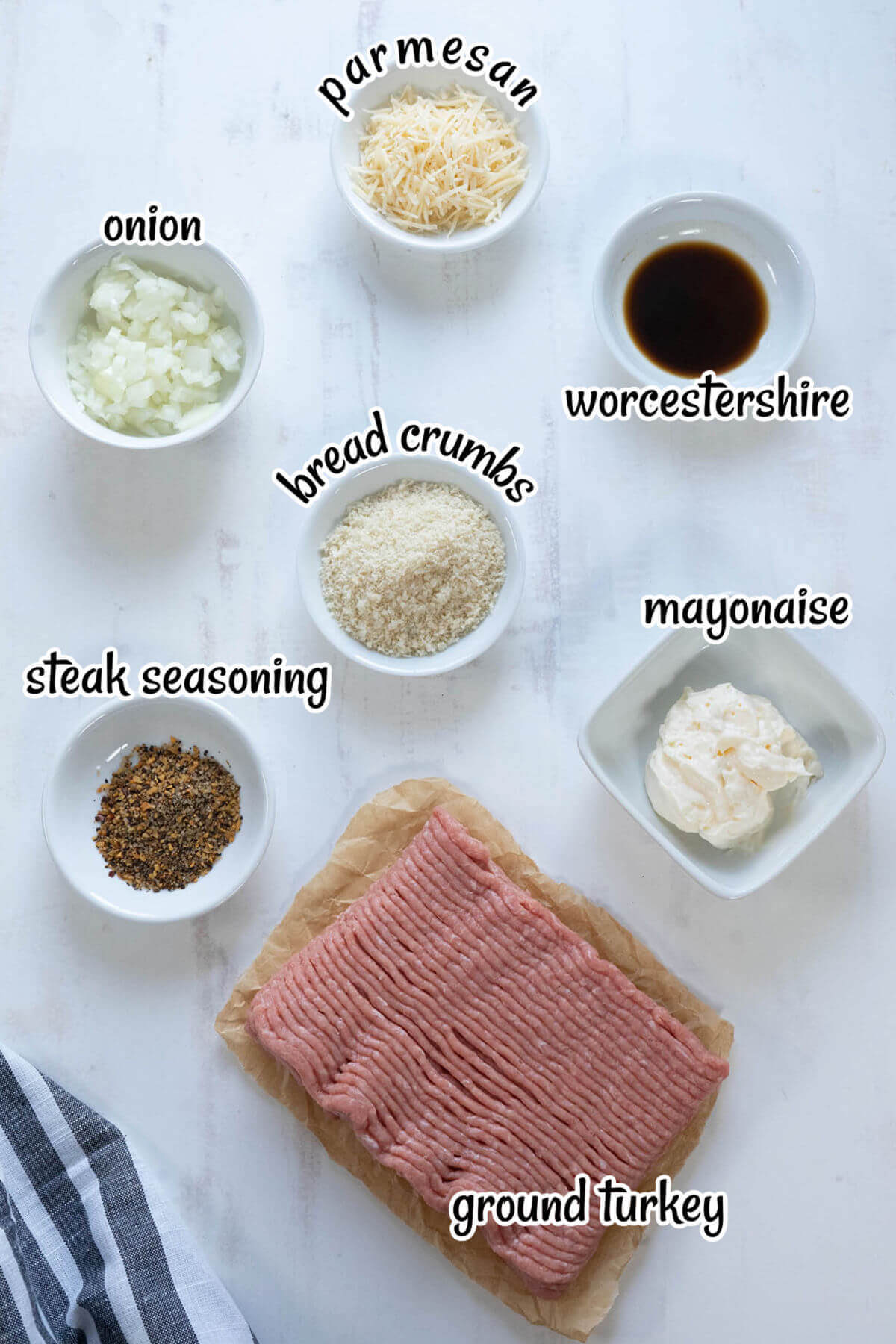 All of the ingredients needed to make grilled turkey burgers laid out on board. With print overlay.