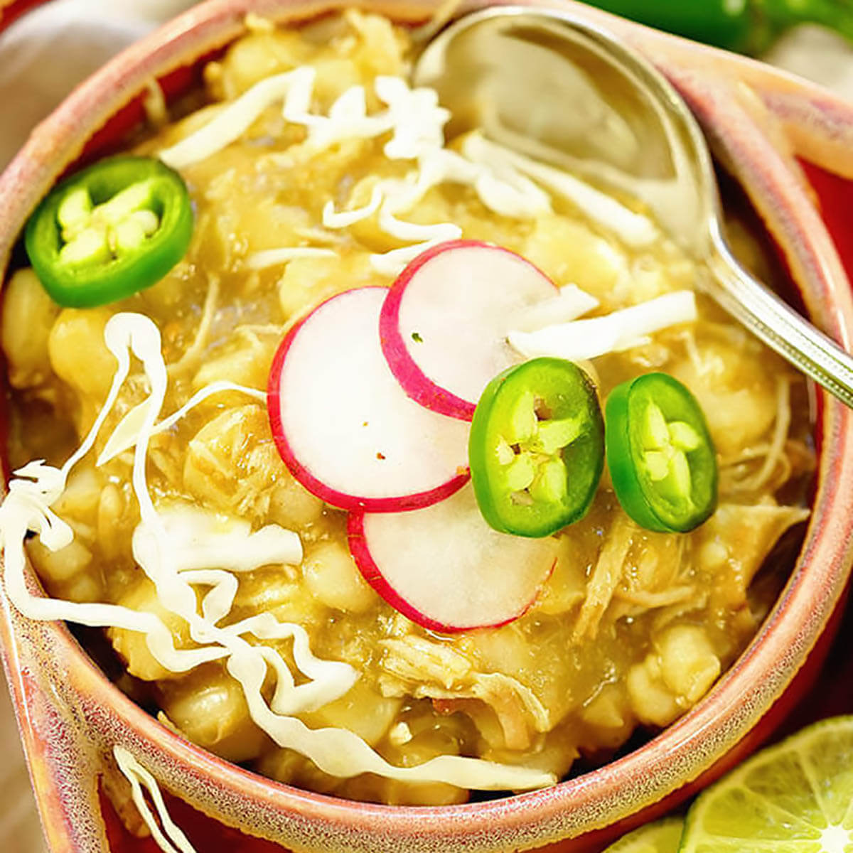 Chicken Posole garnished with jalapeños, with serving spoon.
