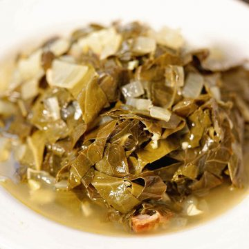 Southern style collard greens piled in a white bowl.