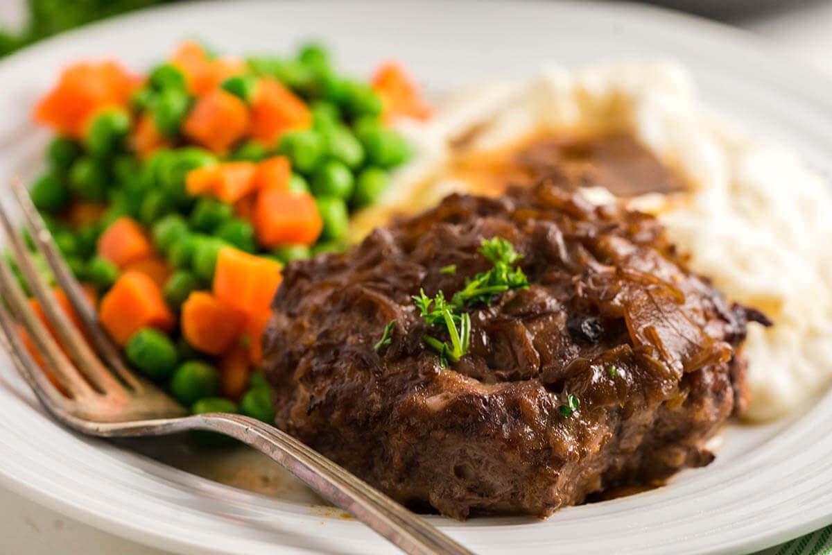 Hamburger steak with brown gravy, potatoes, peas and carrots.