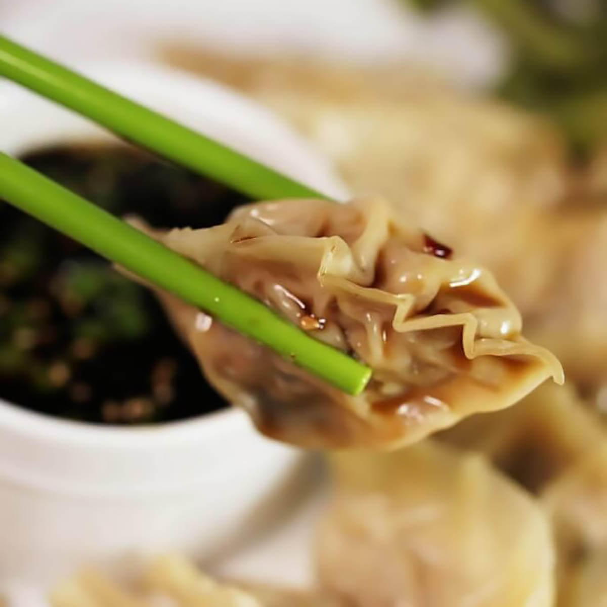 Potsticker held by chopsticks with soy sauce dip in the background.