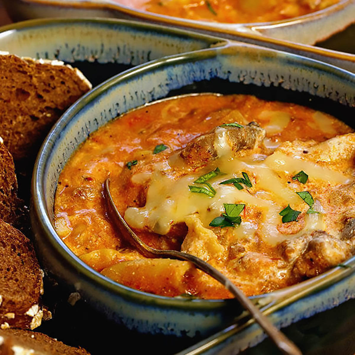 Lasagna soup in bowl topped with cheese with spoon.