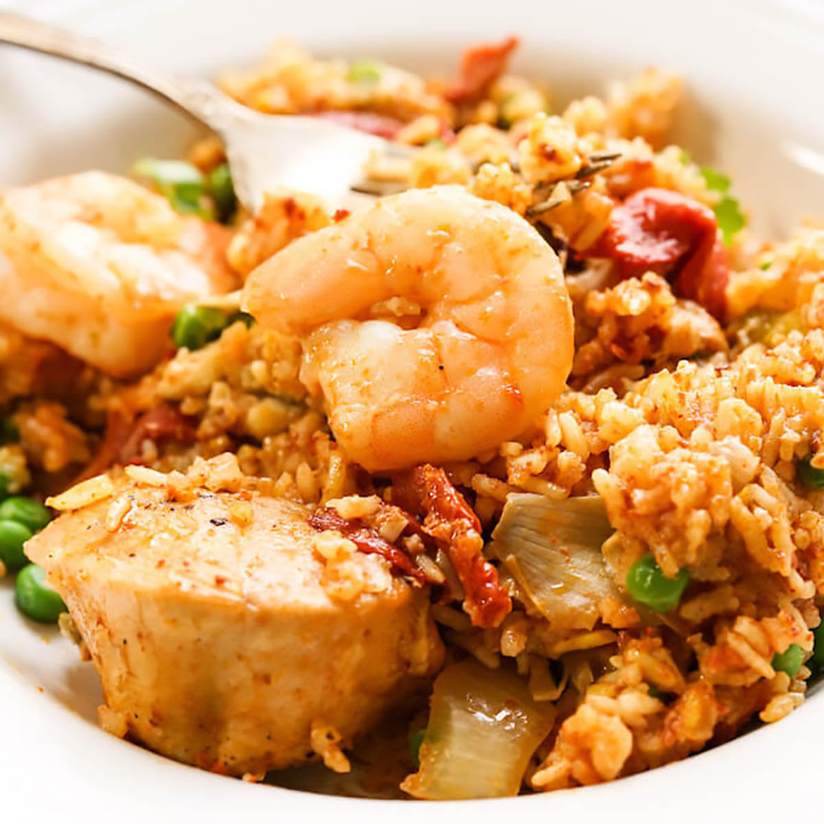 Paella in white bowl with shrimp, pork and chicken.