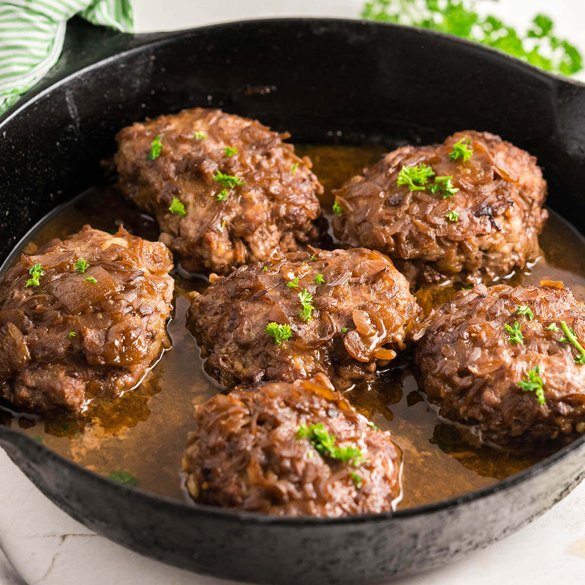 Cast Iron Skillet filled with Salisbury steak with onion gravy.