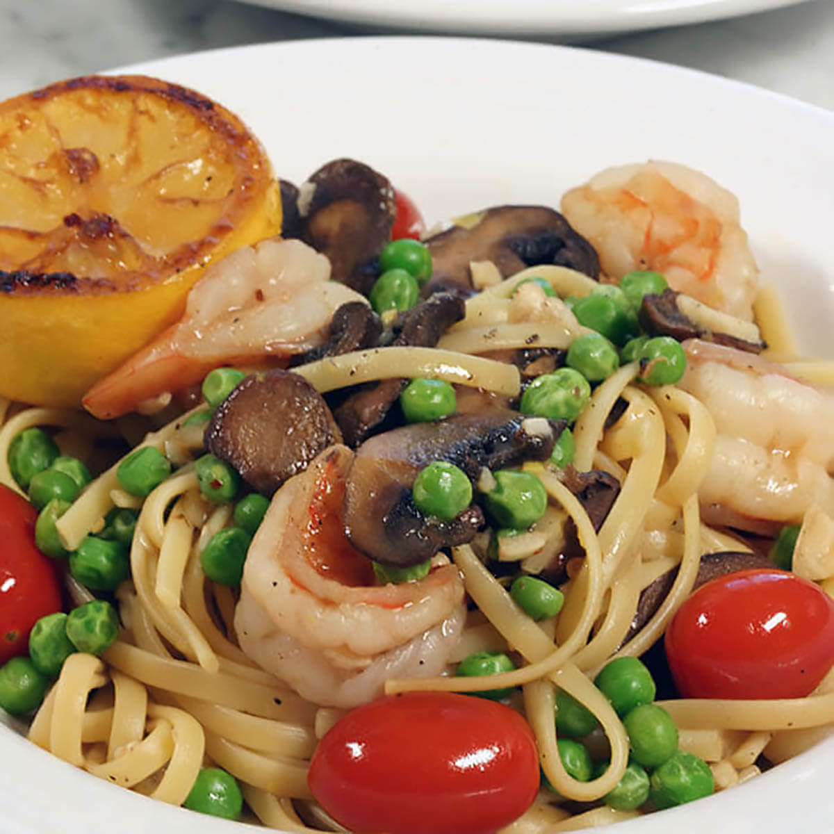 Shrimp Scampi Linguine loaded with vegetables in white bowl.