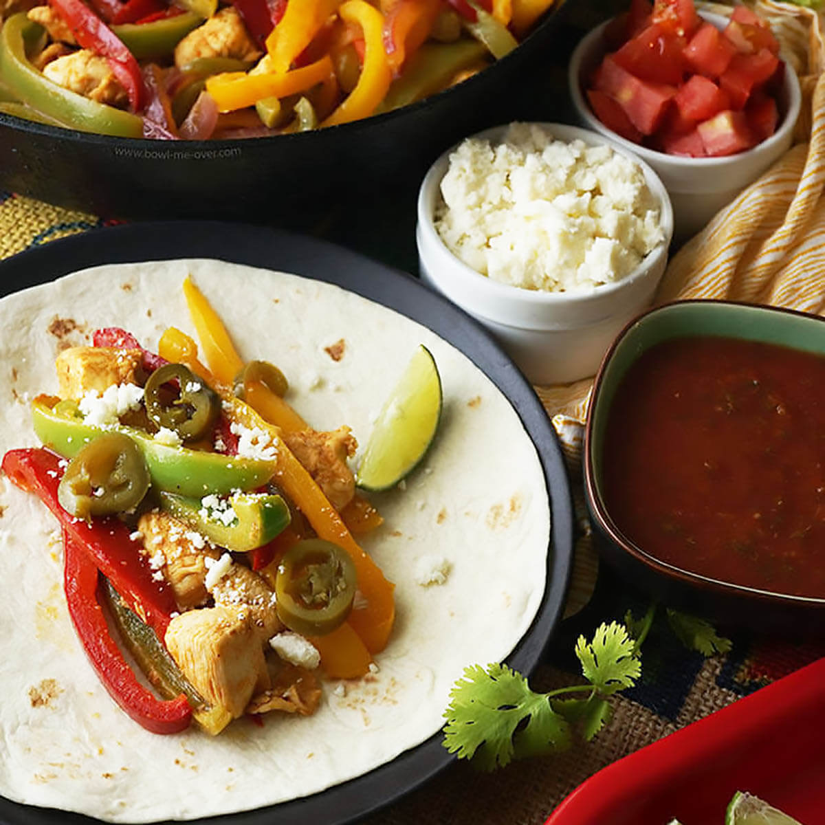 Fajitas on flour tortilla with cheese, tomatoes and sauce for seasoning.