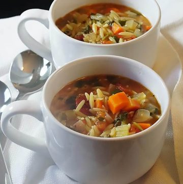 Vegetable Orzo Soup in white bowls with serving spoons.