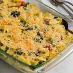 A casserole dish filled with creamy pasta primavera that has a crispy, cheesy topping.