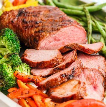 BBQ Tri Tip on platter surrounded by grilled veggies.