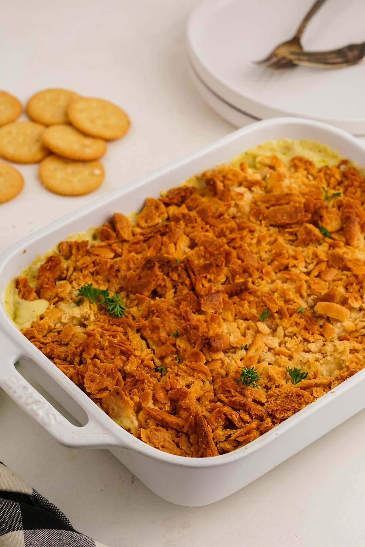 Cooked casserole dish on table with plates and forks ready to serve.