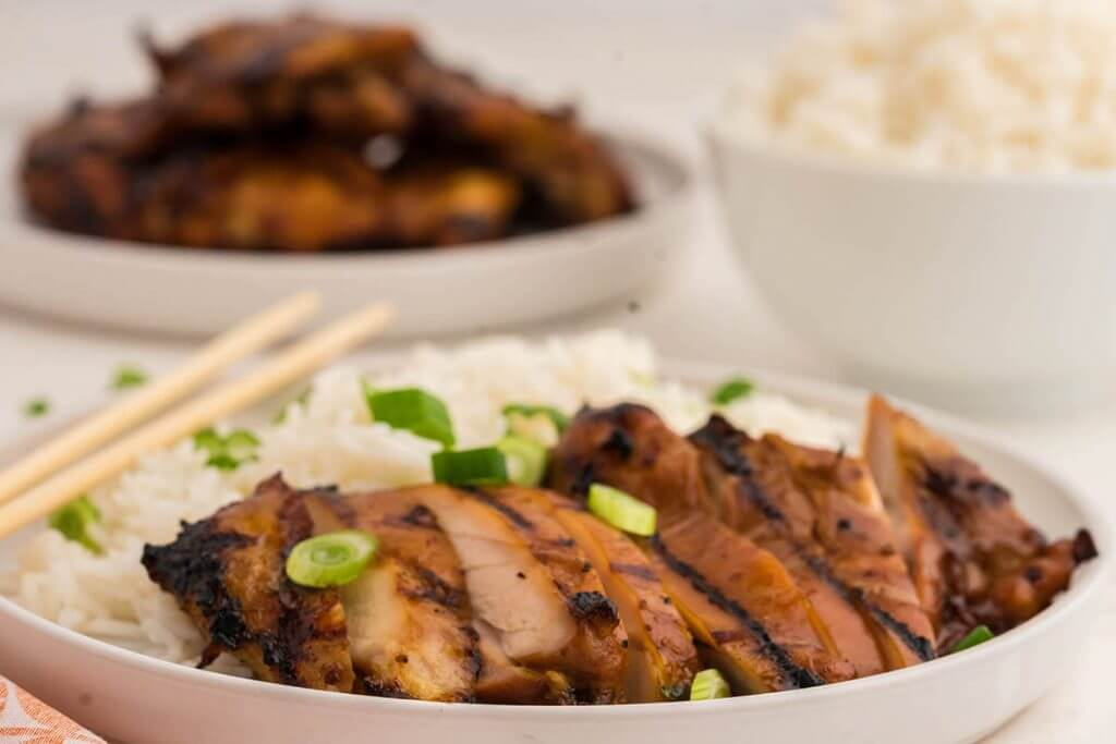Sliced Teriyaki Chicken served with rice and garnished with chopped green onions.