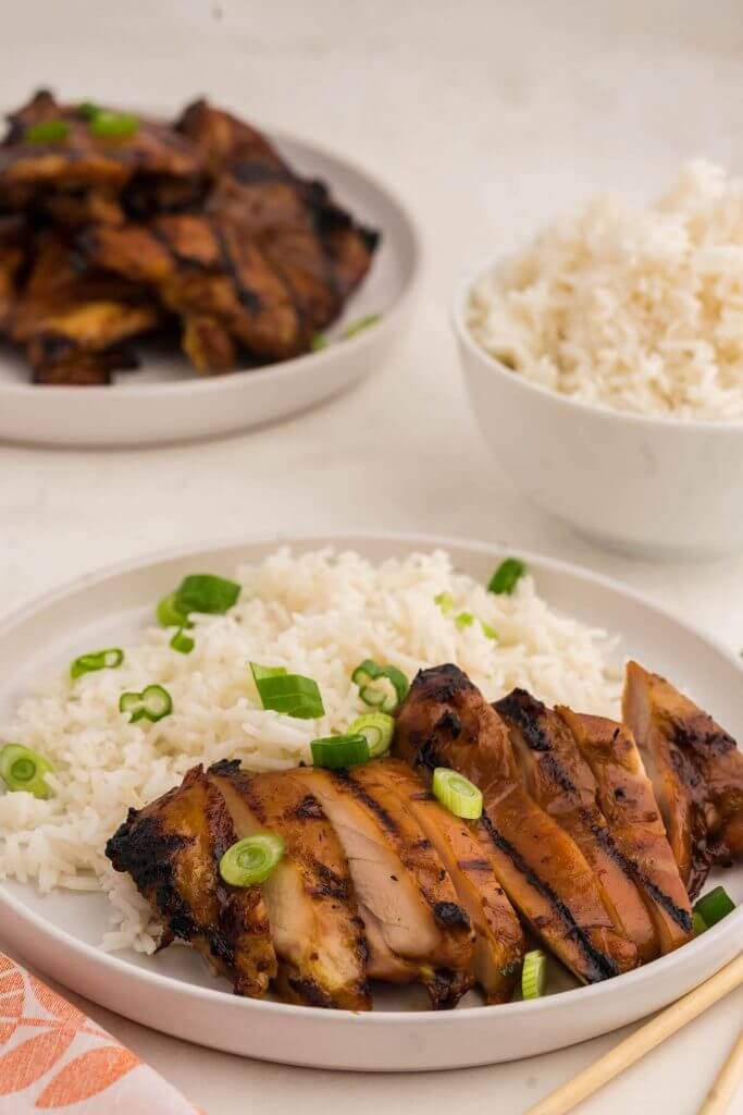 Sliced Teriyaki Chicken thighs on white plate with rice.