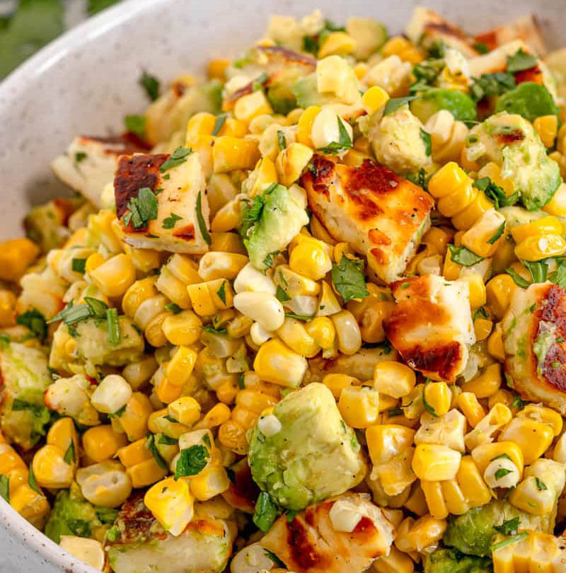 Grilled corn salad in white bowl.