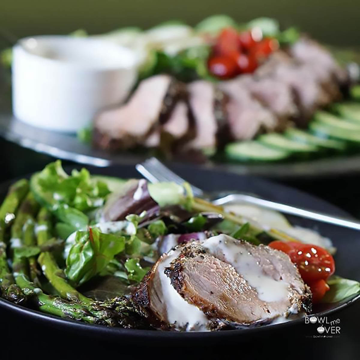 Grilled pork tenderloin on bed of lettuce topped with creamy dressing.